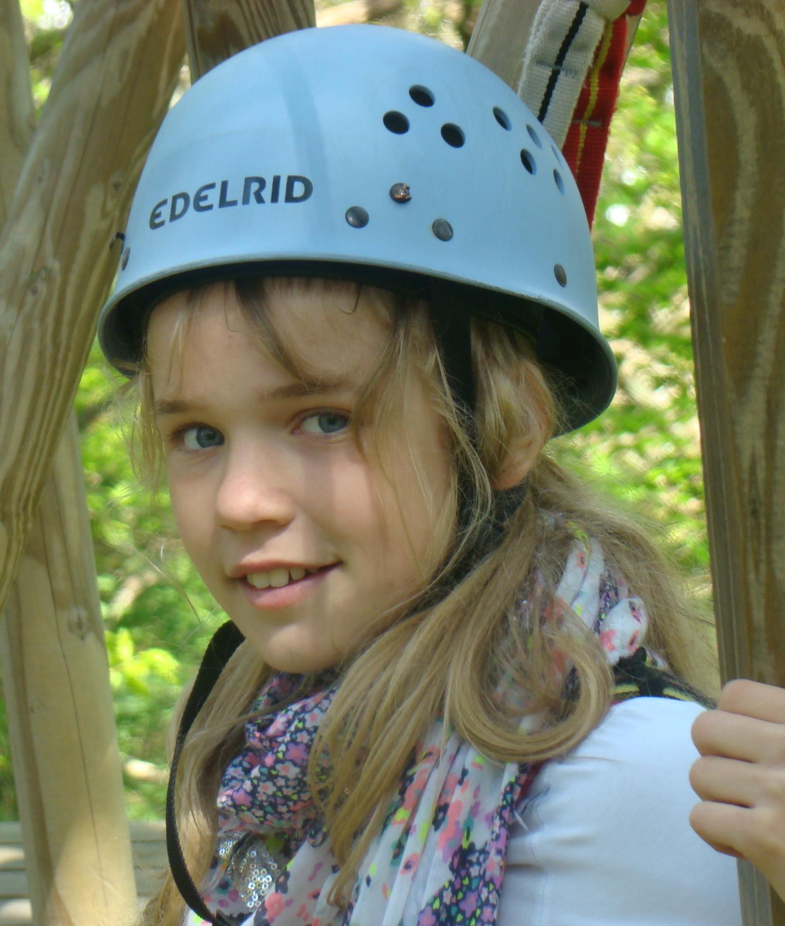 Mädchen mit blauem Helm im Stangenwald im Kletterwald BinzProra