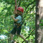 lachendes Mädchen in Seilbahn in Parcours 3 im Kletterwald BinzProra